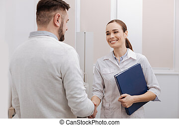 Nice delighted doctor and patient shaking hands