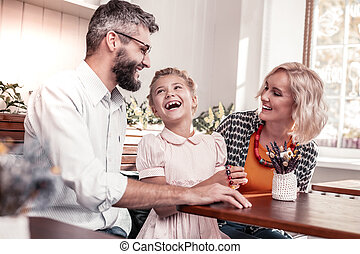 Nice delighted family sitting together at the table