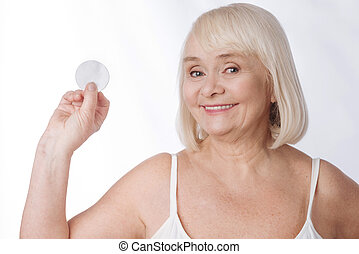 Nice delighted woman holding a cotton pad