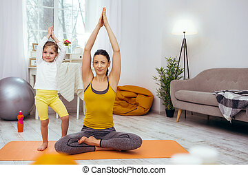 Nice delighted woman practicing yoga at home