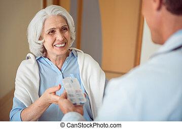 Nice doctor giving medicine his patient