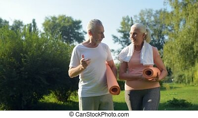 Nice elderlry couple walking in the park with exercises mats