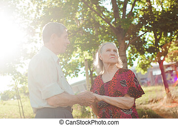 Nice elderly couple in a summer park.