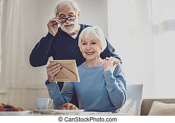 Nice elderly couple looking at the family photo