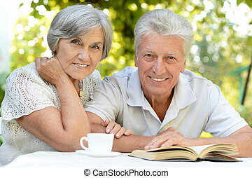 Nice elderly couple sitting at table during summer