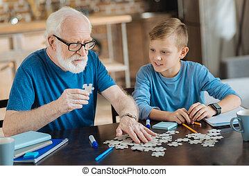 Nice elderly man holding a puzzle piece