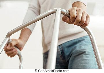 Nice elderly man holding a walking frame