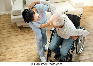 Nice elderly man using caregivers help