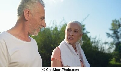 Nice elderly sporty woman walking in the park with her husband