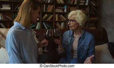 NIce elderly woman and her daughter drinking red wine at home