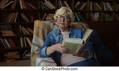Nice elderly woman enjoying reading at home