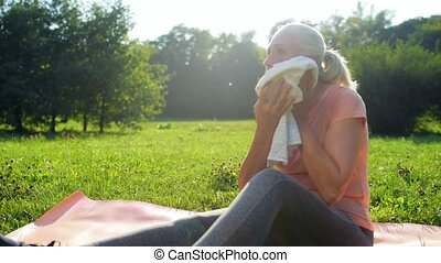 Nice elderly woman resting after sport exercise in the park