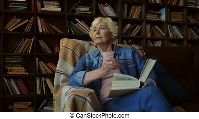 Nice elderly woman sitting in a home library