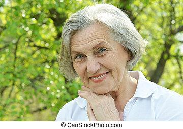 Nice elderly woman resting in summer park