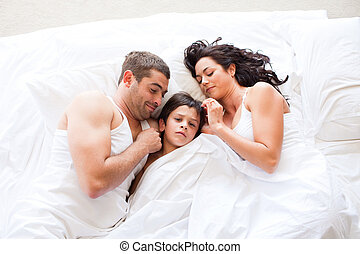 Nice family sleeping together in a white bed