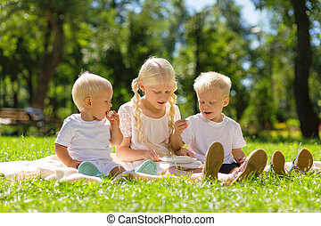 Nice girl and boys sitting in the park all together