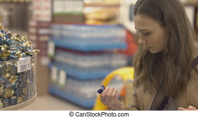 Nice girl chooses sweets at the supermarket