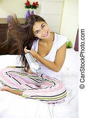 Nice girl drying hair at home in her room