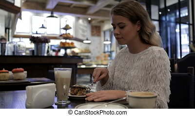 Nice girl eating yummy at the cafe. The girl or woman begin...