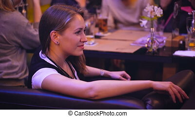Nice girl in a nightclub restaurant spending time with friends.