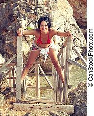 nice girl in bikini near rocks