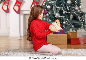 Nice girl playing near Christmas tree