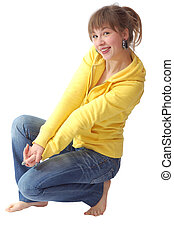 nice girl dressed in blue jeans ans yellow sweater sit down on the floor