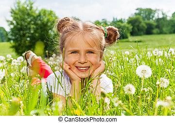 Nice girl smiles laying on a grass