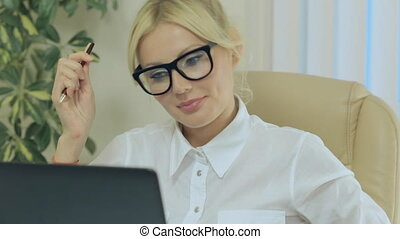 Nice girl smiling and looking at computer screen in office