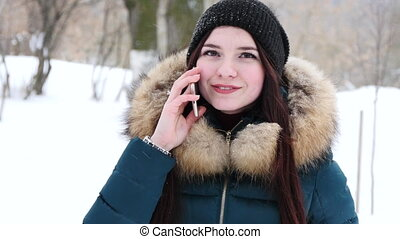 Nice girl speaking by mobile phone in winter park.