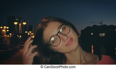 Nice girl with glasses posing on the night embankment in the...