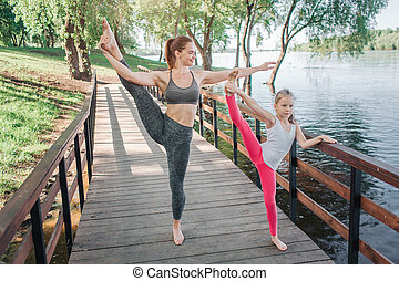 Nice girls are doing the same workout on bridge. They are stretching their right legs up. Small girl is holding her hand on barrier while young woman is pulling it to the side nad looking there.