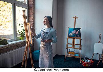 Nice good looking woman creating art in the studio