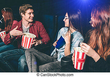 Nice guy is proposing his popcorn to a girl. Two girls are looking at him and smiling. Brunette girl is impressed. She is holding a cup of coke while her friend has a small basket of popcorn.