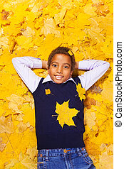 Nice happy boy in autumn maple leaves