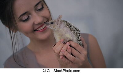 Nice hedgehog in woman hands on natural photosession outdoors