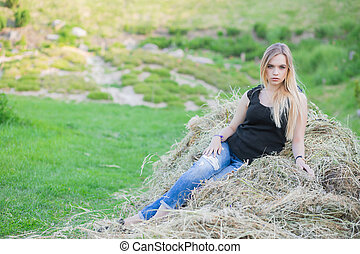 Nice lady posing sitting on the hay.