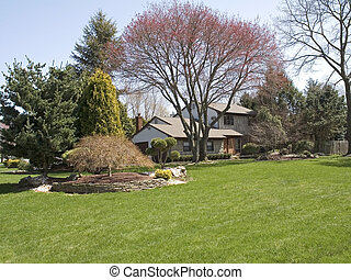 This is a view of a beautiful home with a big front yard and nice landscaping.