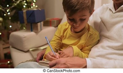 Nice little boy preparing Christmas presents with his grandfather