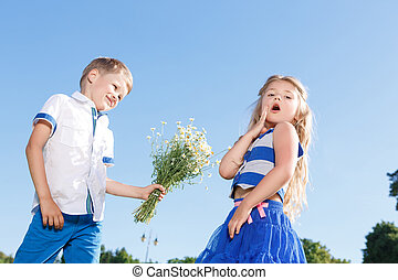 Nice little boy presenting flowers