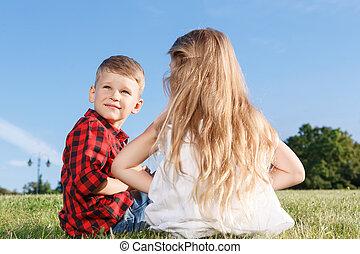 Nice little girl and boy sitting backwards