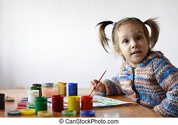 little girl draws paint in the room