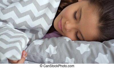 Nice little girl sleeping in bed