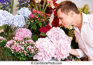 Nice man smelling the flowers