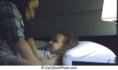 nice mother gives an anterior kiss to her child before going to bed, gently hugs the child and cover her very sweetly with a blanket and turns off the lamp. 4K