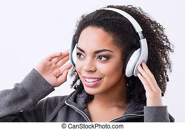 Nice mulatto woman listening to music - Feel the beat....