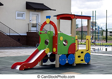 Nice new bright colorful plastic slide in shape of big car or train in empty kindergarten yard on sunny summer day on modern nursery building background. Children outdoors activities concept.