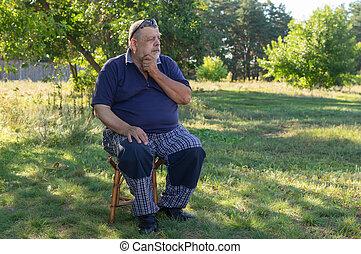 Ukrainian thoughtful senior man sitting on a stool in summer garden
