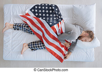 Nice patriotic man sleeping with American flag