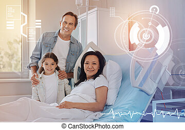 Nice picture of a friendly family smiling in a modern hospital